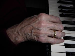 Why Worry--older woman's hand on musical keys