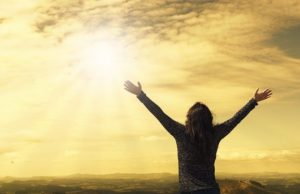 Staying Positive in a Negative World-woman with hands raised, facing the sun